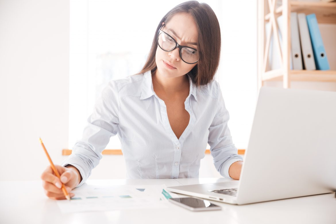 graphicstock-photo-of-businesswoman-dressed-in-white-shirt-sitting-in-her-office-and-writing-notes