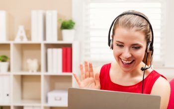 happy-young-woman-with-headset-talking-on-her-laptop
